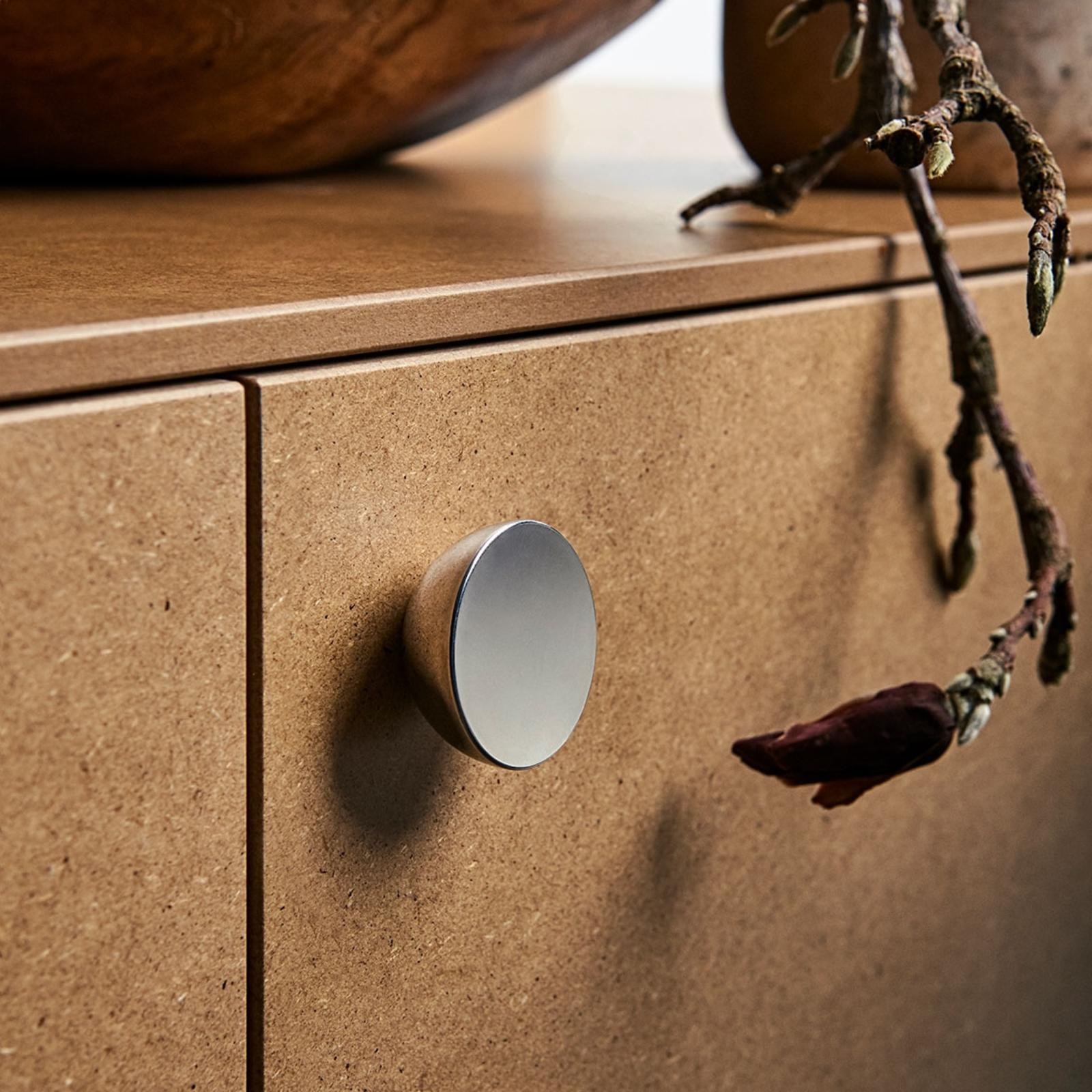 Hemisphere shaped knob in shiny metal, on cabinet fronts in clear-coated mdf