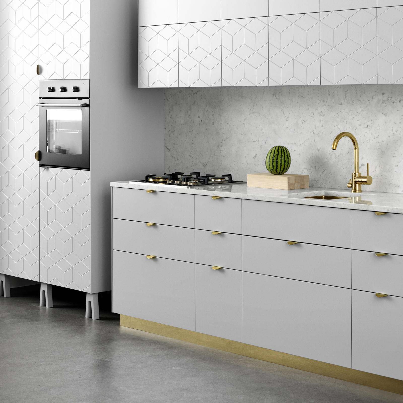 Kitchen built from Ikea's Metod frames, with light grey furniture legs and a plinth in brass