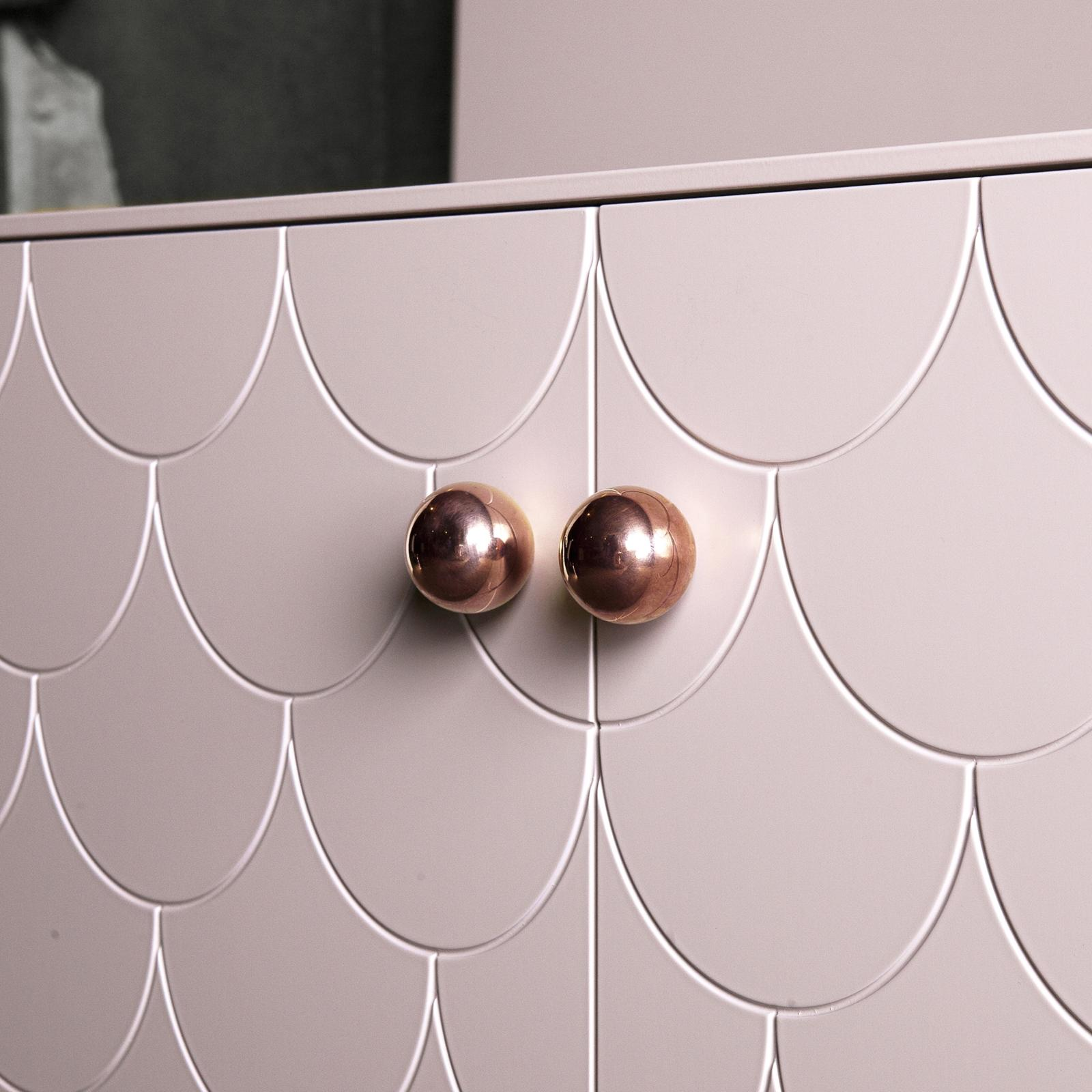 Handle in copper on a pink sideboard with a pattern that resembles fish scales
