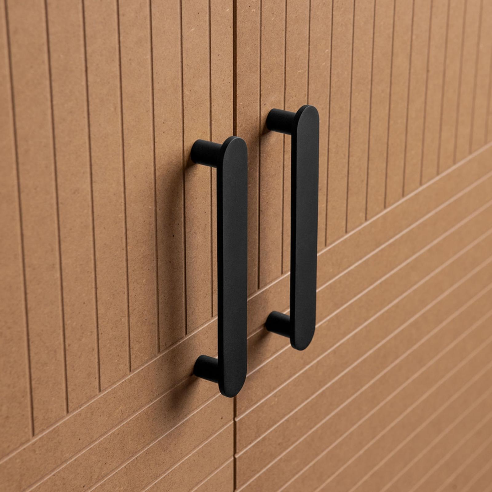 Elongated, matte black handles on wardrobe fronts from Superfront