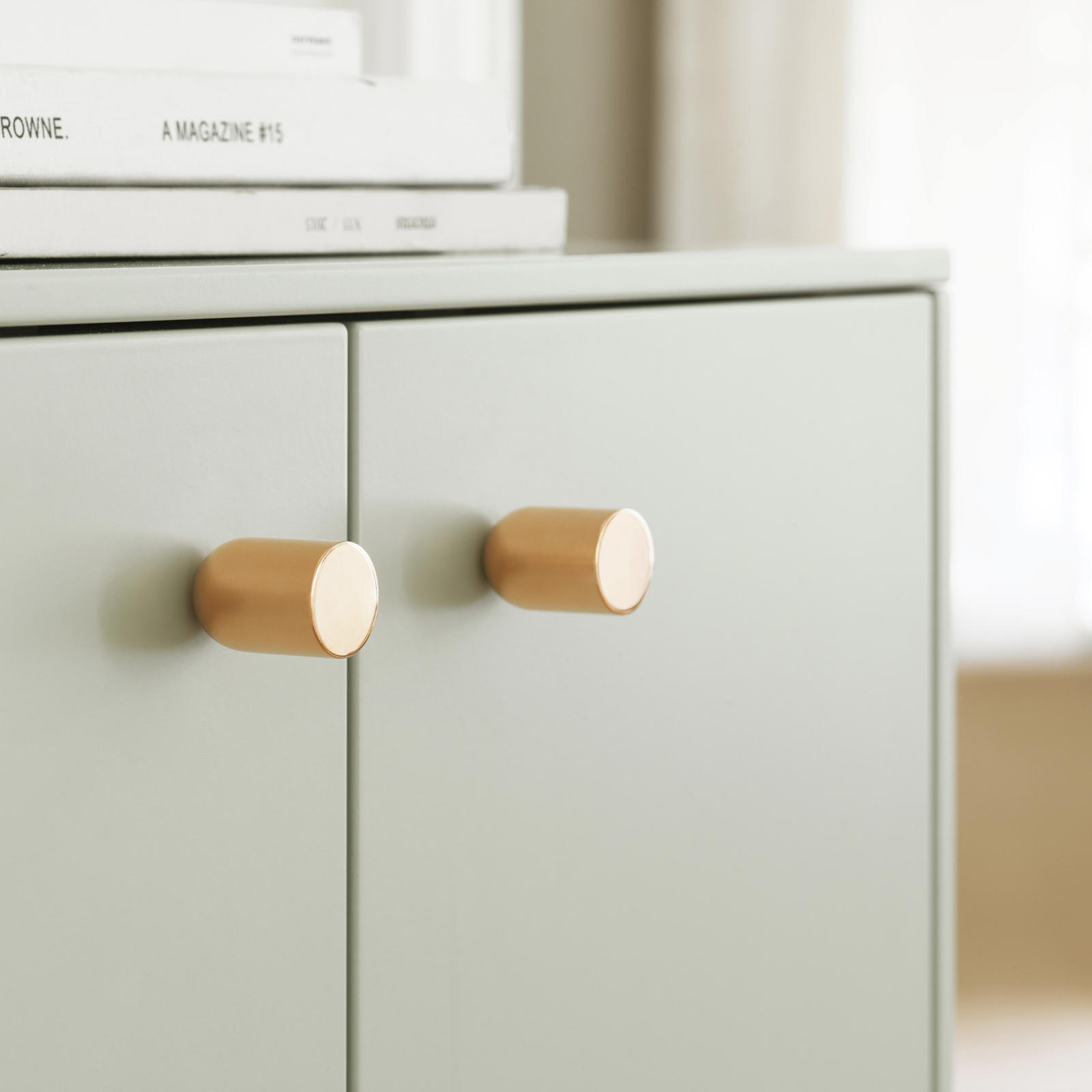 Knob in brass on a pale green front from Superfront