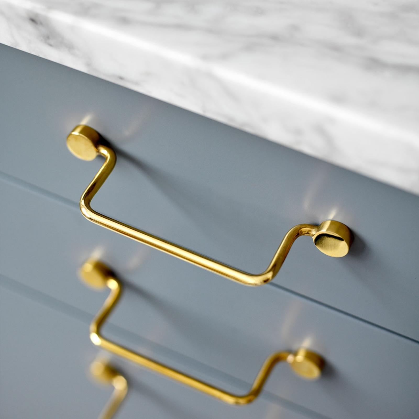 Classic handles in brass from Superfront, mounted on grey kitchen drawers