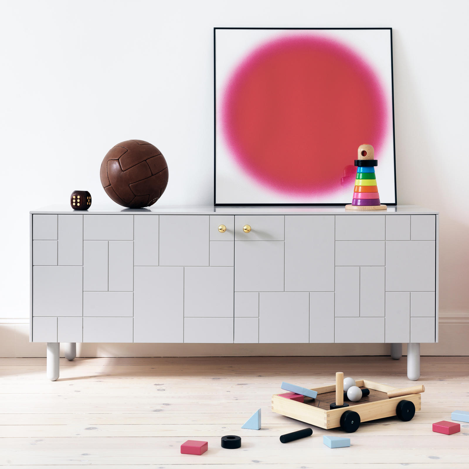 Sideboard in children's room with cube patterned fronts and minimalist furniture leg in grey