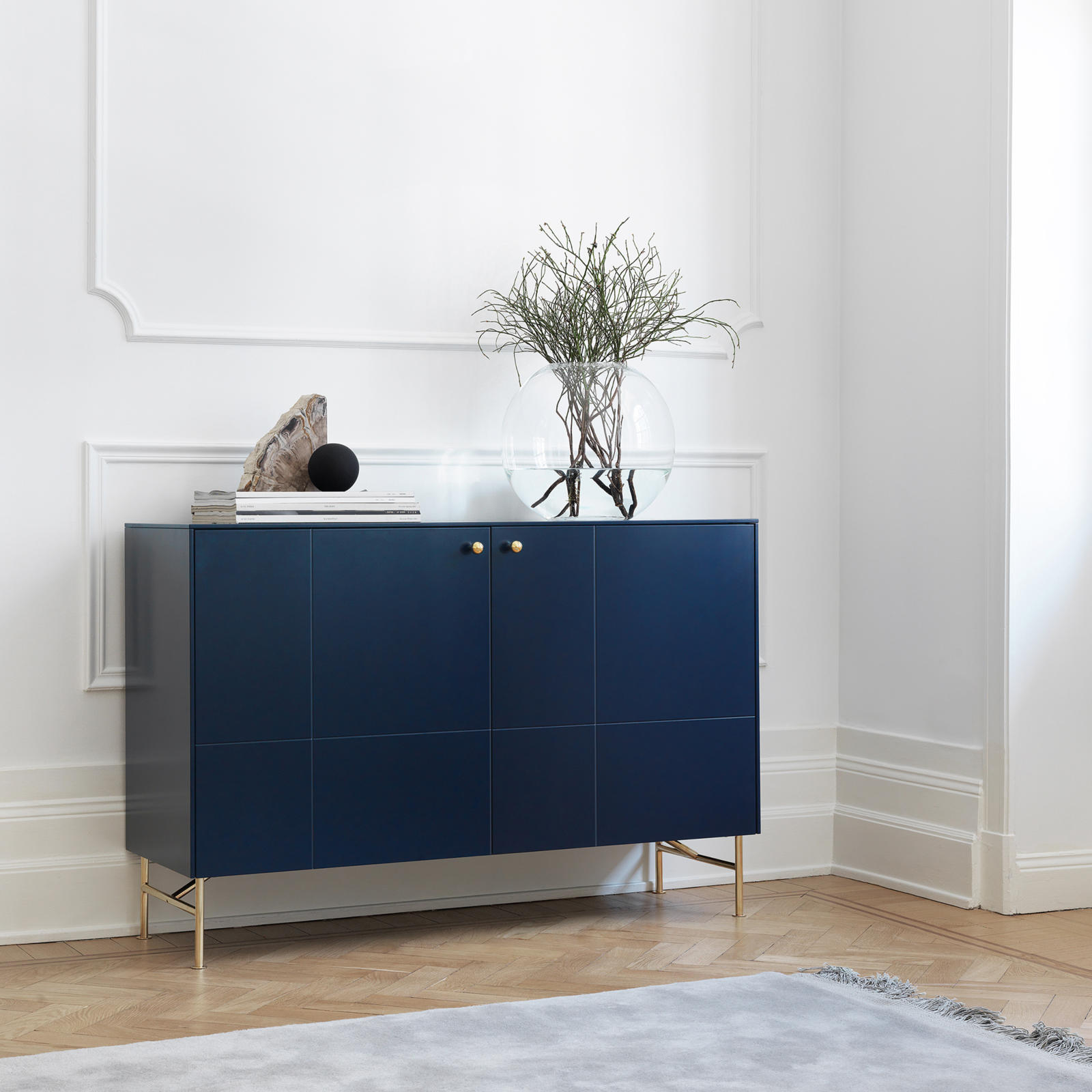 Dark blue sideboard in a living room, with handles and legs in brass