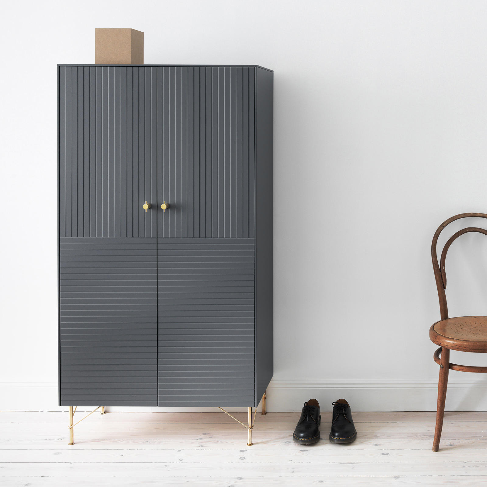 Grey cabinet with a pattern formed by vertical and horizontal lines, knobs and furniture legs in solid brass